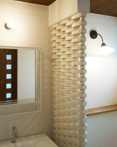 上質なホワイトでまとめた洗面室の画像。鏡と照明が見えています。