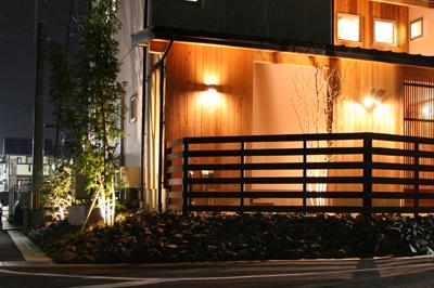 天然木の外壁を照らす照明とライトアップされた植栽がある共感住宅レイアウトの注文住宅の夜の外観