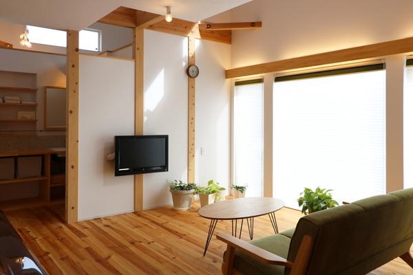 観葉植物が似合うナチュラルな注文住宅のリビング。壁掛けテレビとシンプルなローテーブル、こだわりの緑色のソファがあります。