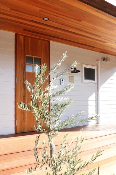 岡崎市の注文住宅、北欧風の白い家の玄関ポーチにはデッキ風の木の階段があります