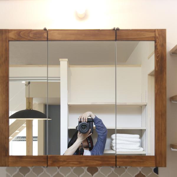 洗面の鏡の前でカメラを構える共感住宅レイアウトの清水