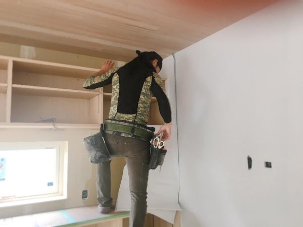 岡崎市で注文住宅をつくる共感住宅レイアウトの建築中のおうち。クロスを貼っている職人さんが丁寧なプロの仕事をされています。